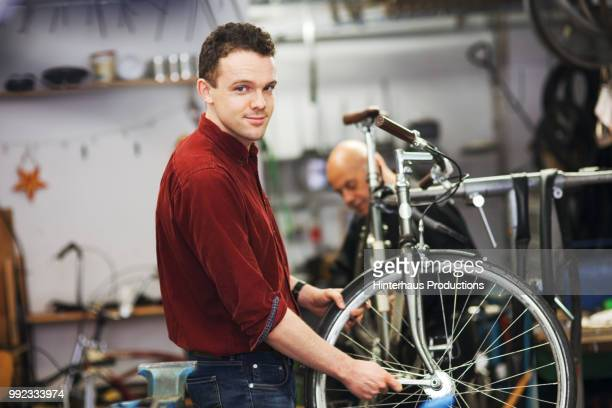 young bike technician working on bicycle - hingabe stock-fotos und bilder