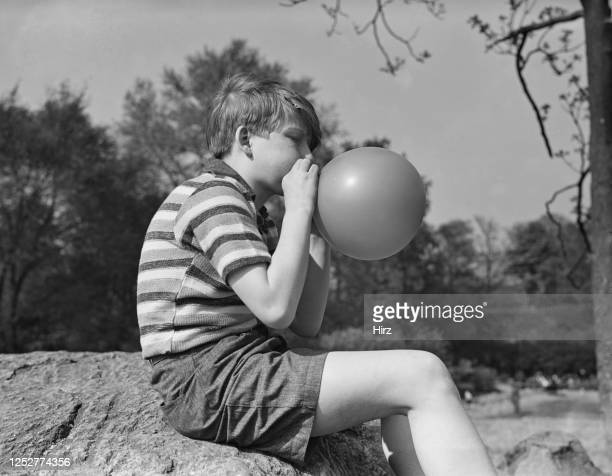 Young Billy Redfield blows up a balloon in New York State May 1937