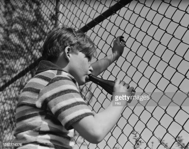 Young Billy Redfield takes a drink from a bottle while peering through a fence in New York State May 1937