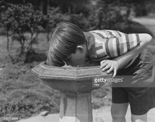 Young Billy Redfield takes a drink from a public drinking fountain in New York State May 1937