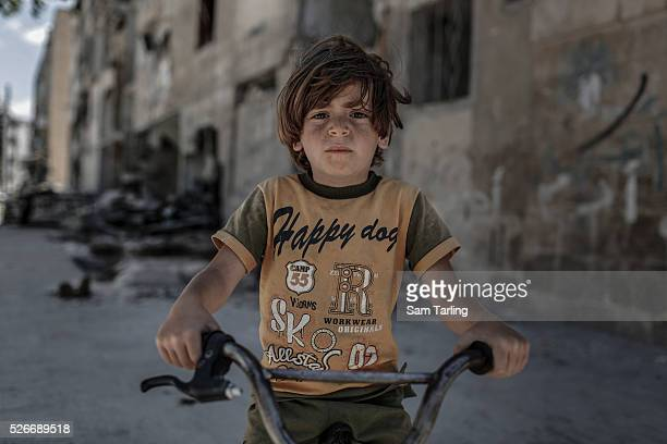 A young bit plays in the Hanano neighbourhood of Aleppo on June 3 2014 Hanano has been one of the districts worst affected by barrel bombs and other...