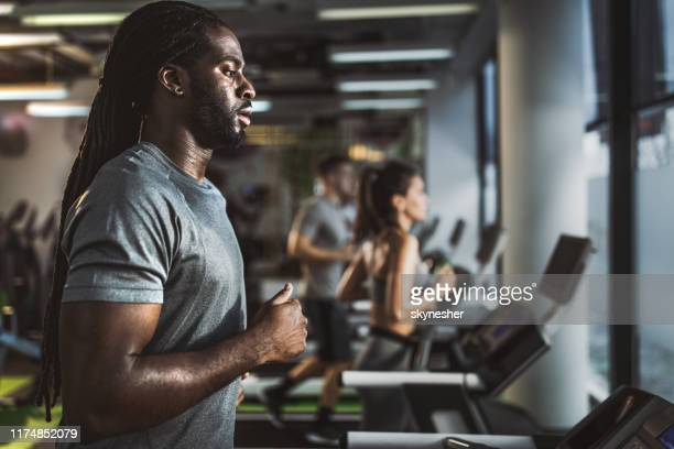 young black athlete running on treadmill in a gym. - warming up stock pictures, royalty-free photos & images