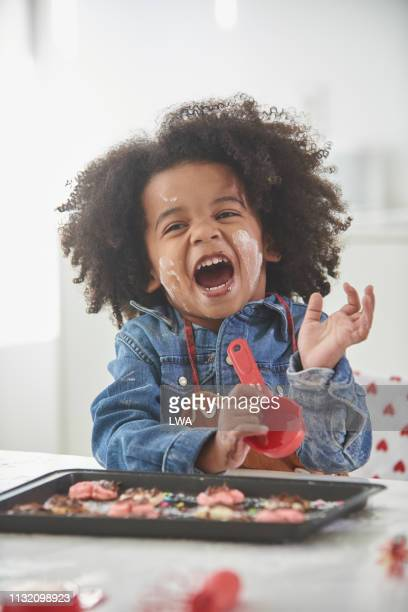 young black boy baking in kitchen. - naughty valentine stockfoto's en -beelden