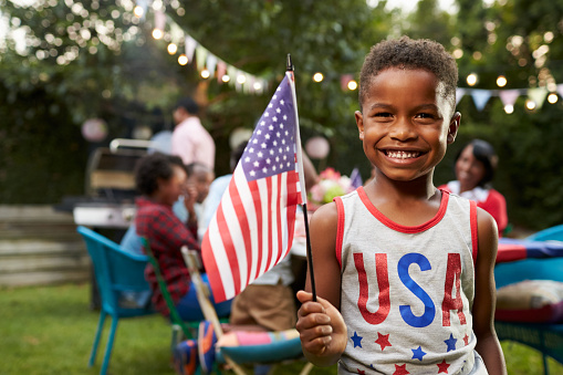 Young black boy holding flag at 4th July family garden 638288282