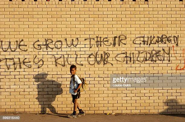 A young Black boy in Johannesburg walks past a wall covered with graffiti reading 'We Grow Their Children They Kill Our Children' The slogan was...