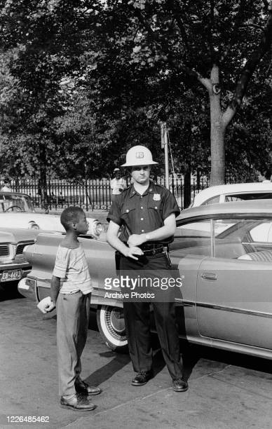 Young Black boy talking to a police officer in Harlem, New York City, during the Harlem Riots, July 1964. The riots were sparked by the killing of...