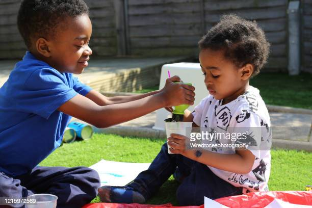 young black boys squeezing paint into a pot in the garden - children only stock pictures, royalty-free photos & images
