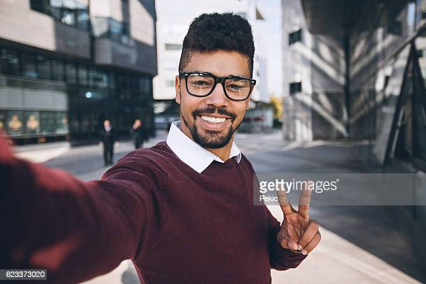 Young black business man taking funny selfie