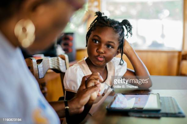 young black child getting help with her homework - evento relativo all'istruzione foto e immagini stock