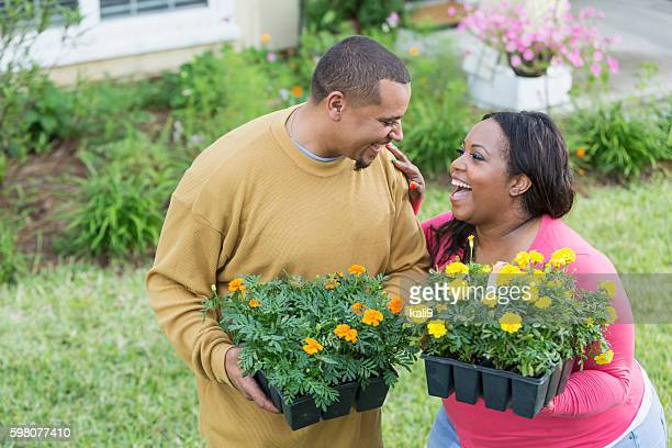 Young black couple outside home planting flowers