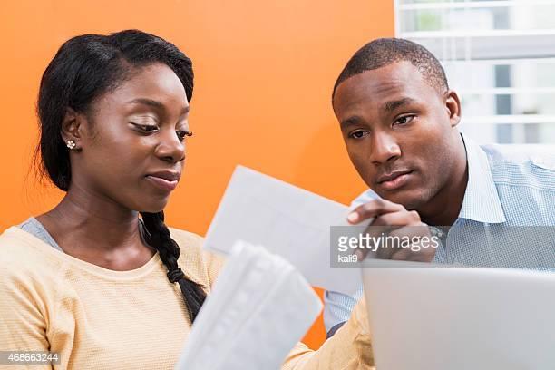 Noir jeune couple de payer les factures à la maison