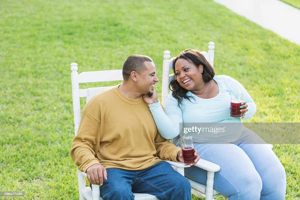 Young black couple sitting, talking, drinking : Stock Photo