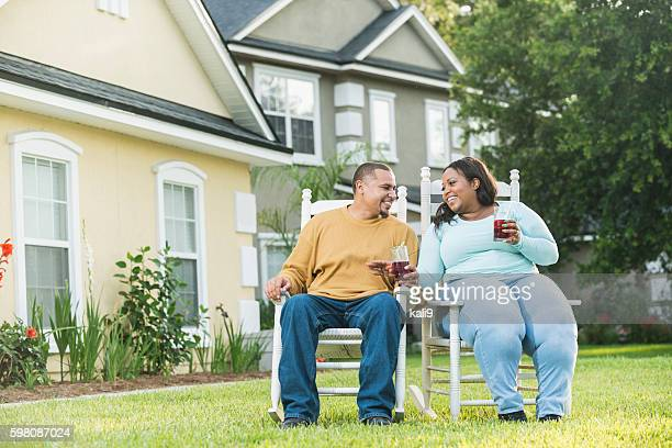 Young black couple sitting, talking, drinking