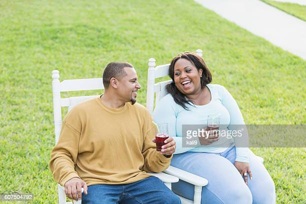 young black couple sitting, talking, drinking - fat woman sitting on man stock pictures, royalty-free photos & images