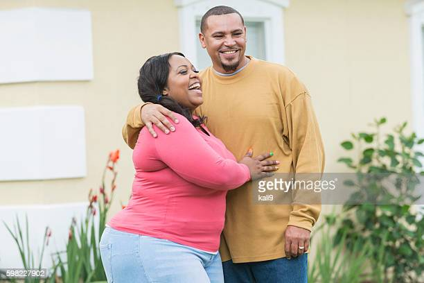 young black couple standing outside home - chubby men stock photos and pictures
