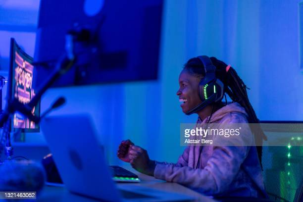 young black female gamer celebrates at night - atmospheric mood stock pictures, royalty-free photos & images