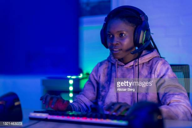 young black female gamer playing at night - africa stock pictures, royalty-free photos & images