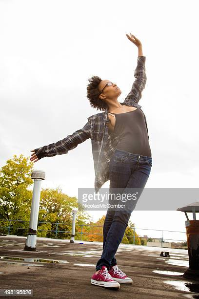 Young black female student practicing her dance moves on rooftop