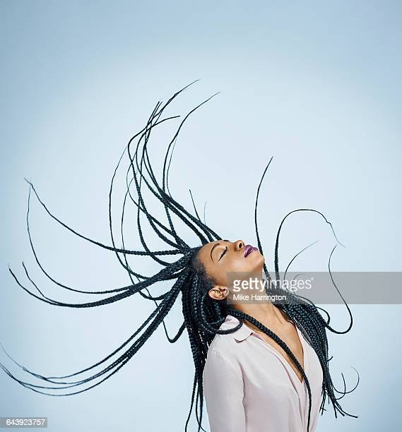 Young black female whipping hair backwards