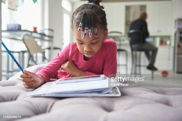 a young black girl does school work from her home. - leanincollection stock pictures, royalty-free photos & images
