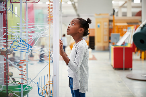 Young black girl looking at a science exhibit, close up 973292450