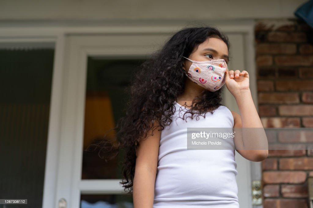 Young black girl wearing face mask outdoors : Stock Photo