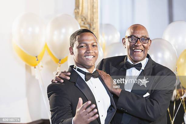 Young black Hispanic man with father in tuxedos