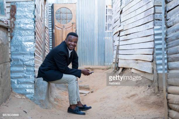 young black male sits and checks his mobile phone - black alley stock photos and pictures