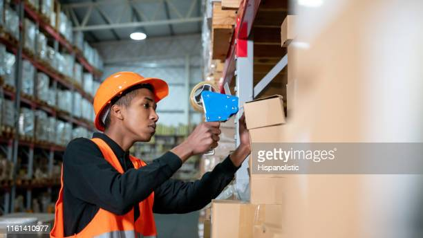 young black male working at a distribution warehouse closing boxes with adhesive tape - hispanolistic stock photos and pictures