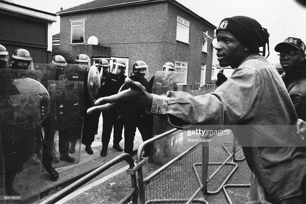 A young black man arguing with police in riot gear who are guarding the British National Party (BNP) headquarters in south east London, during a demonstration over a racist murder in Eltham, 8th May 1993.