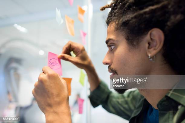 Young black man at the office planning and sticking ideas to the glass window for the business
