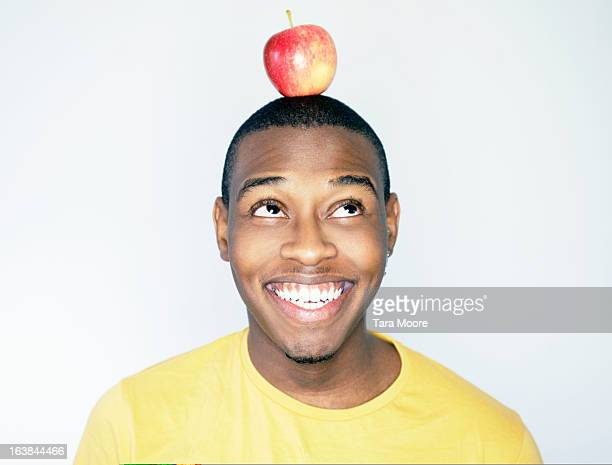 young black man balancing apple on head and smilin