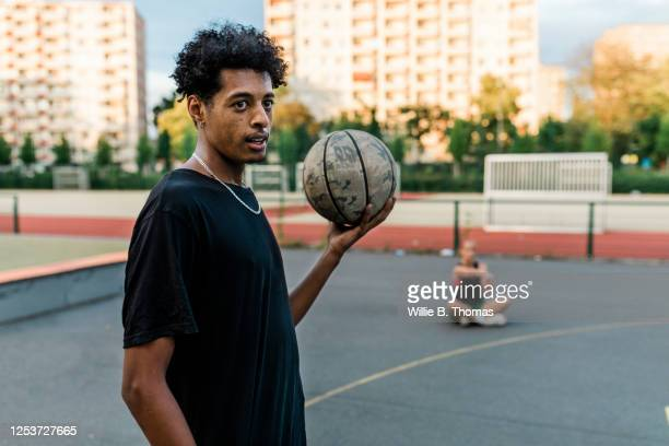 young black man holding basketball - basketball sport stock pictures, royalty-free photos & images