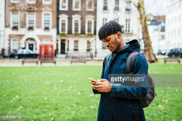 Young black man in London using smart phone for communication