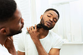 Young black man looking at mirror and shaving beard with trimmer