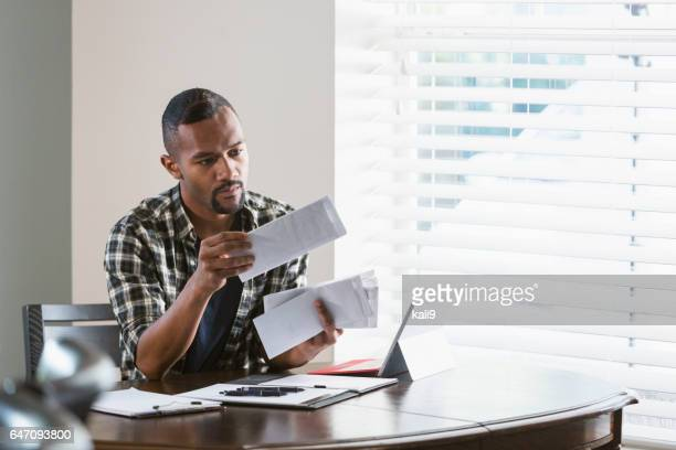 Young black man paying bills at home
