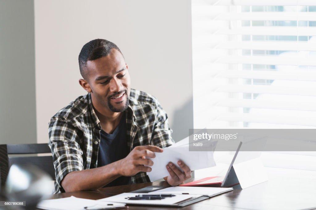 Young black man paying bills at home : Stock Photo