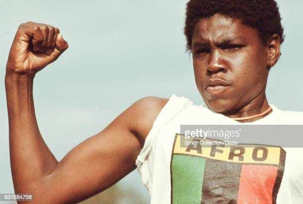 A young black man showing his muscles and wearing an Afro t shirt at a community program for youths in the South Side of Chicago Illinois August 1973...