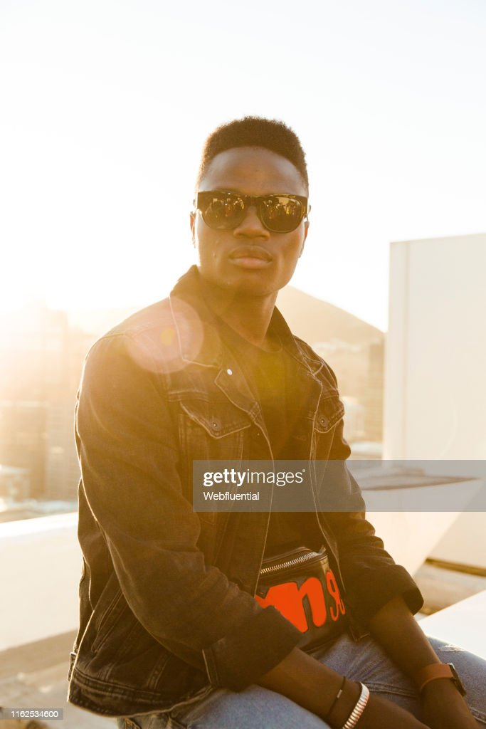 Young black man sitting on a roof top during sunset : Stock Photo