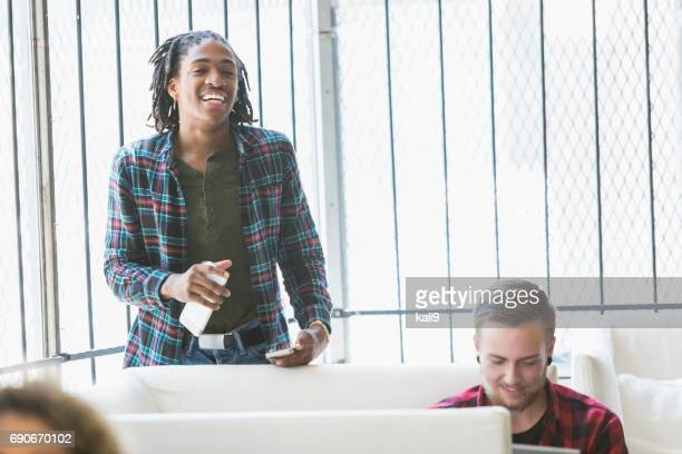 Young black man smiling in office holding mobile phones