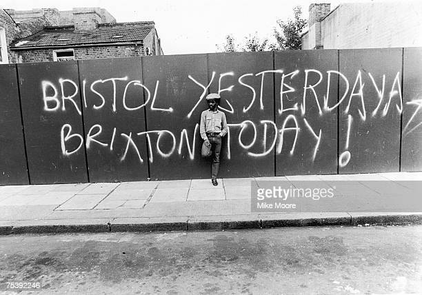 A young black man standing in front of a fence with a graffiti message of racial unrest 4th August 1980