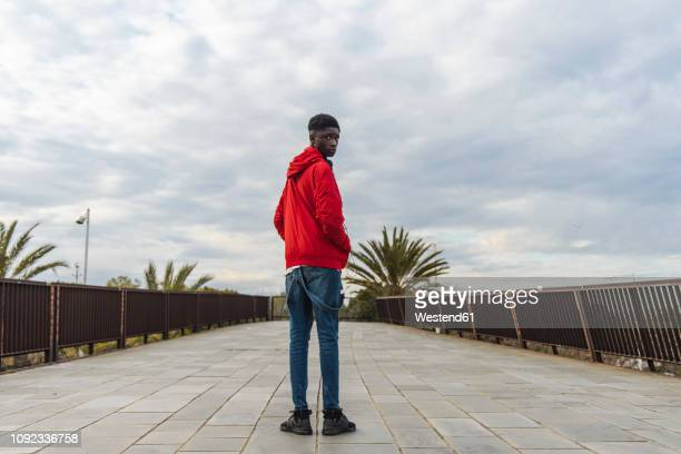 young black man standing outdoors, looking over shoulder - jaqueta - fotografias e filmes do acervo