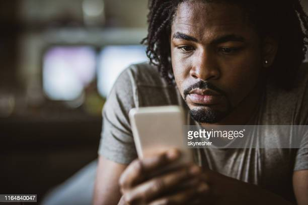 young black man text messaging on smart phone at home. - candid forum stock pictures, royalty-free photos & images