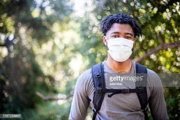 young black man wearing a face mask while hiking - adamkaz stock pictures, royalty-free photos & images