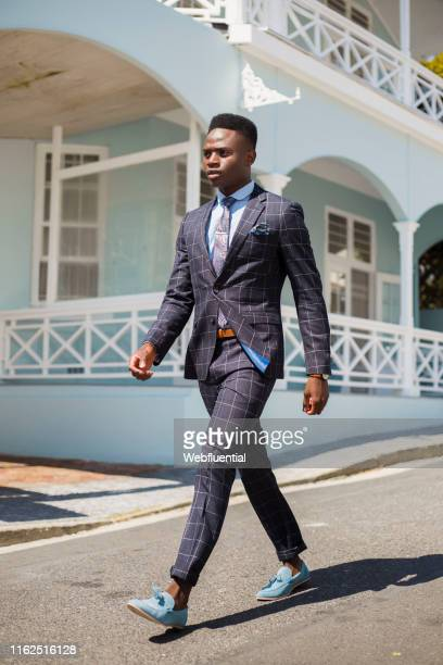 young black man wearing a suit suit walking outdoors - webfluential stock pictures, royalty-free photos & images