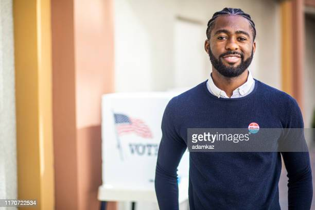 私はステッカーに投票した若い黒人の男 - コーンロウ ストックフォトと画像