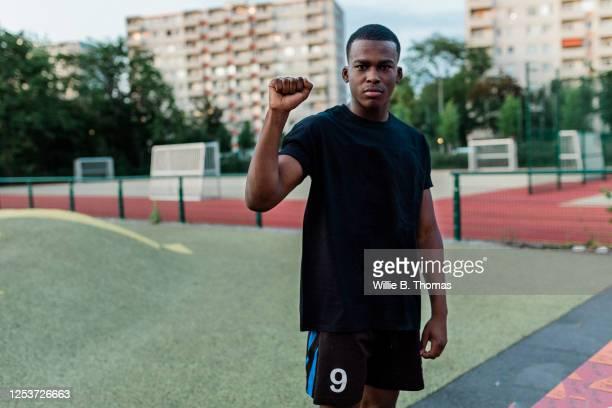 young black man with raised fist - antirracismo fotografías e imágenes de stock