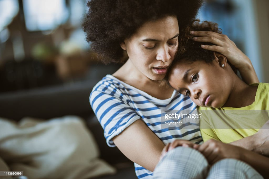 Young black mother taking care of her sad little daughter at home. : Stock Photo