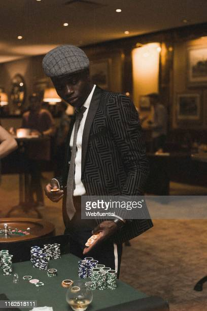 Young black South African man in suit playing poker