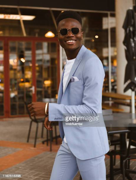 Young black South African man wearing a blue suit and sunglasses indoors